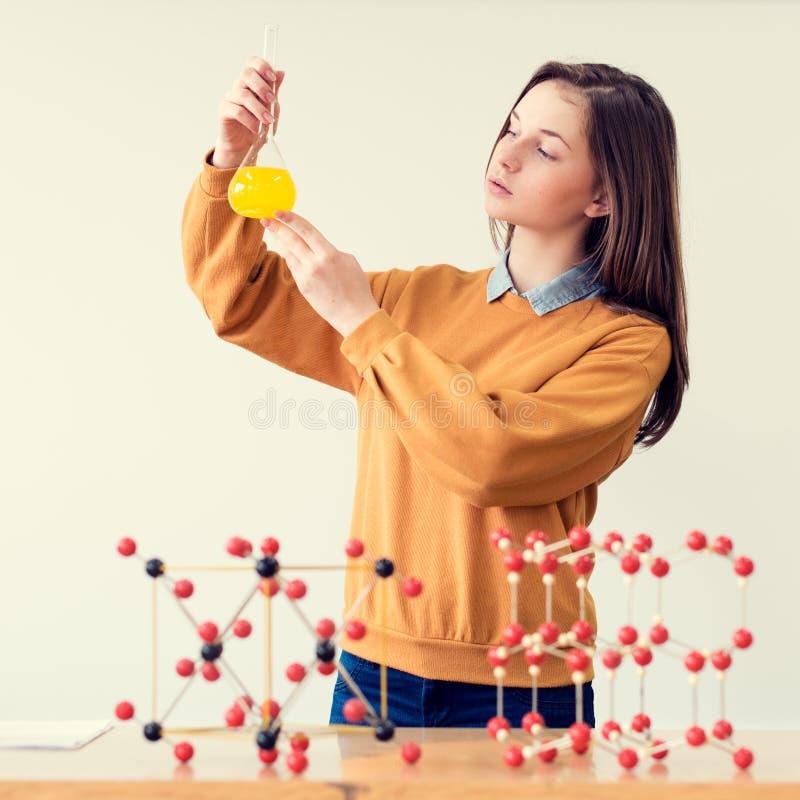 Vrij jonge Kaukasische student die in het chemielaboratorium werken De chemieglaswerk van de studentholding royalty-vrije stock foto's