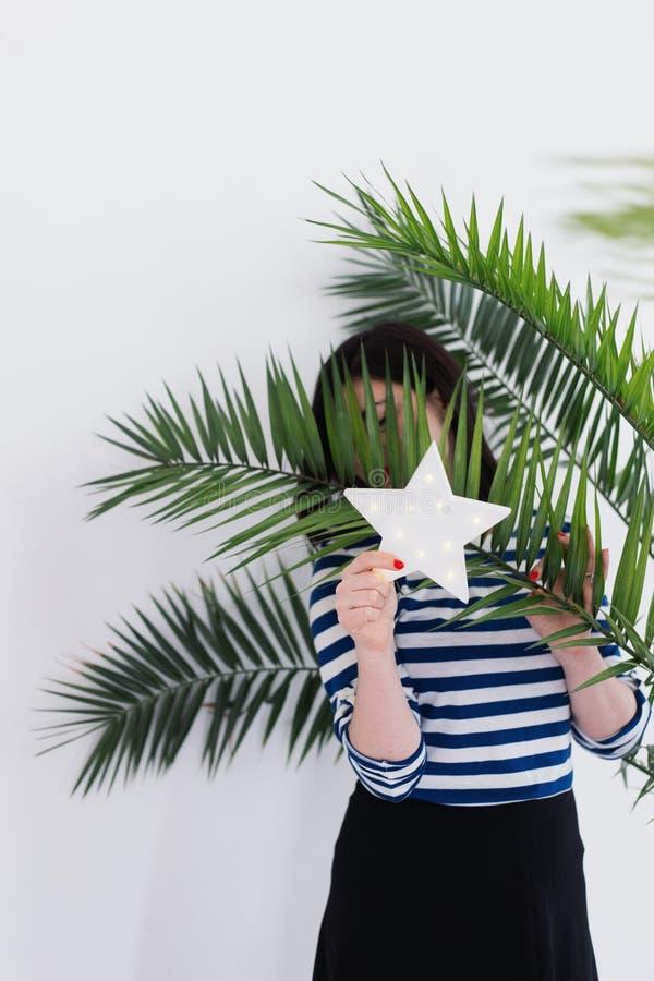 Vrij jonge Kaukasische vrouw in het gestripte vest verbergen achter witte LEIDENE gloeiende ster en groene palmbladen royalty-vrije stock afbeelding