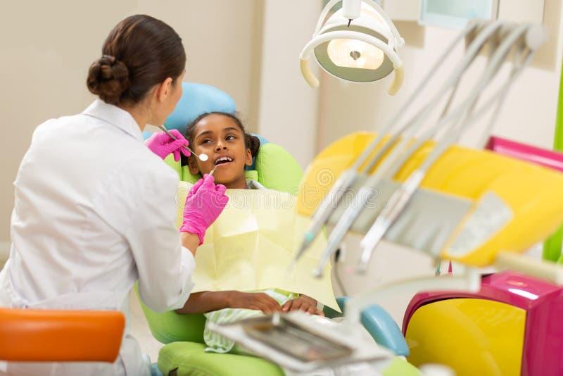Vrij jonge meisjeszitting calmly als tandartsenvoorzitter stock afbeelding
