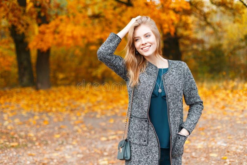 Vrij jonge modieuze mooie vrouw in in elegante grijze laag in modieuze groene blouse op een gang in openlucht in het park stock afbeelding