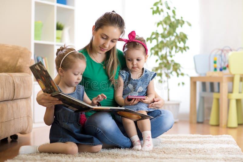 Vrij jonge moeder die een boek lezen aan haar dochters royalty-vrije stock foto