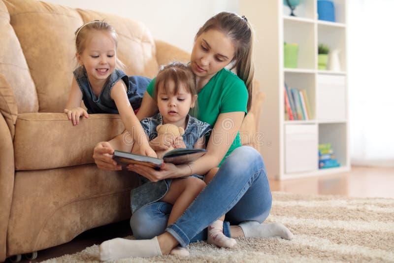 Vrij jonge moeder die een boek lezen aan haar dochters stock fotografie