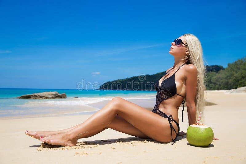 Vrij jonge slanke vrouw op strand dichtbij blauw schoon water stock foto