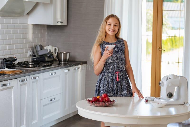Vrij jonge tiener die een fruit smoothie in de keuken drinken royalty-vrije stock fotografie