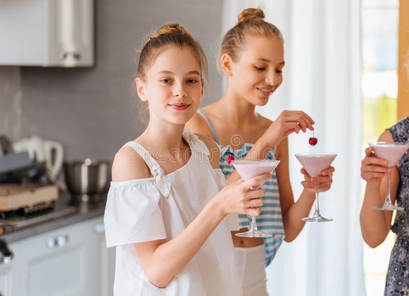 Vrij jonge tiener die een fruit smoothie in de keuken maakt stock foto