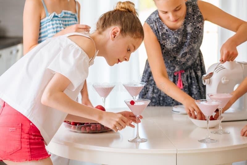 Vrij jonge tiener die een fruit smoothie in de keuken maken stock afbeeldingen