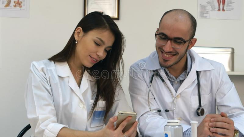 Vrij jonge verpleegster die iets tonen grappig op haar telefoon aan mannelijke collega stock afbeeldingen