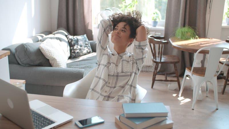 Vrij jonge vrouw die aan moderne die laptop werken door boeken thuis wordt omringd royalty-vrije stock fotografie