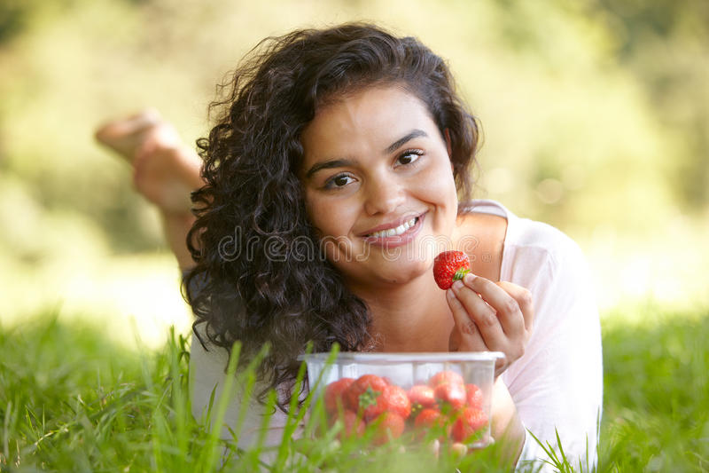 Vrij Jonge Vrouw die Aardbeien in openlucht eten royalty-vrije stock afbeeldingen