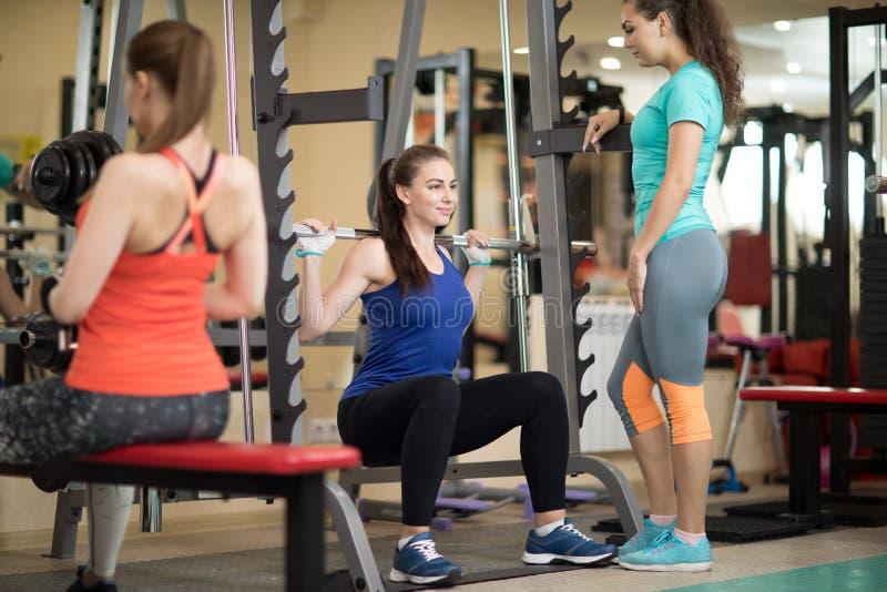 Vrij jonge vrouw die barbell in gymnastiek gebruiken De trainer houdt horloge over haar stock foto's