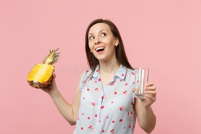 Vrij jonge vrouw die in de zomerkleren omhoog de greephelft van verse rijpe die het glaskop kijken van het ananasfruit op roze wo royalty-vrije stock afbeeldingen