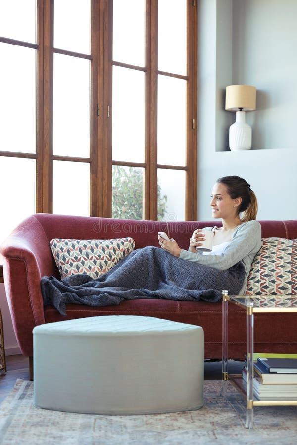 Vrij jonge vrouw die door het venster kijken terwijl thuis het gebruiken van haar mobiele telefoon op bank royalty-vrije stock afbeeldingen