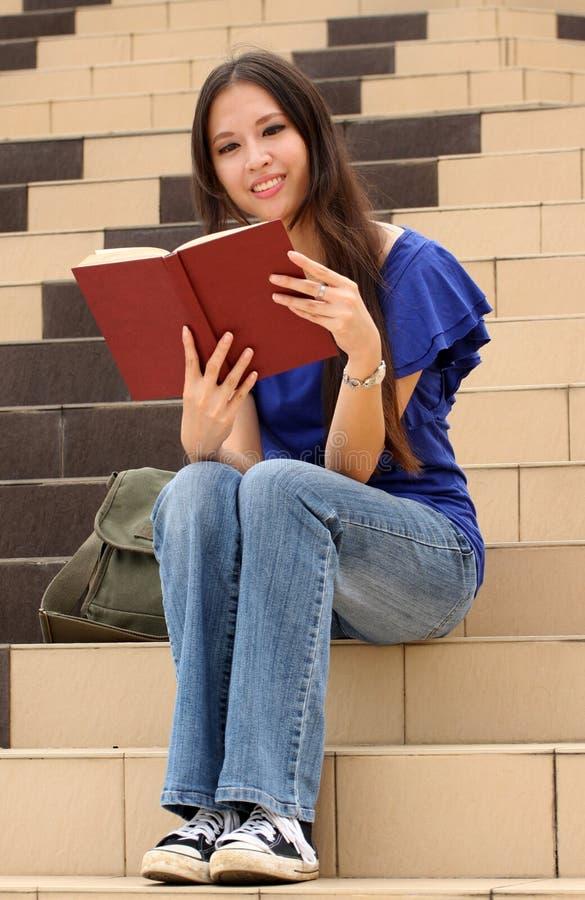 Vrij jonge vrouw die een boek leest bij trap stock afbeeldingen