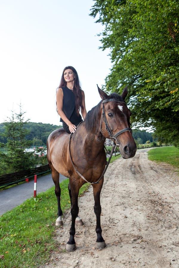 Vrij jonge vrouw die een bruin paard berijden stock foto