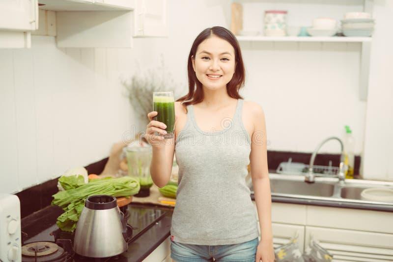 Vrij jonge vrouw die een plantaardige smoothie in haar keuken drinken stock afbeeldingen