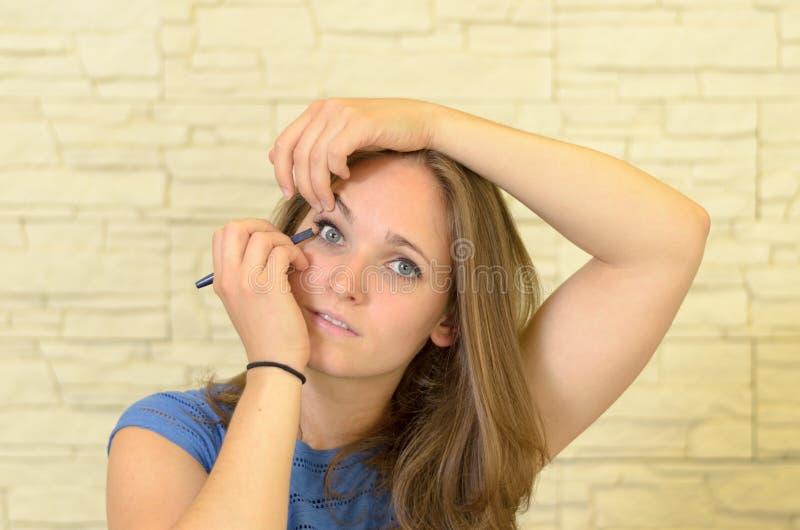 Vrij jonge vrouw die eyeliner toepassen stock afbeeldingen