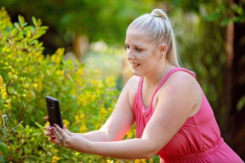Vrij Jonge Vrouw die Foto's van Haar Tuin nemen royalty-vrije stock fotografie