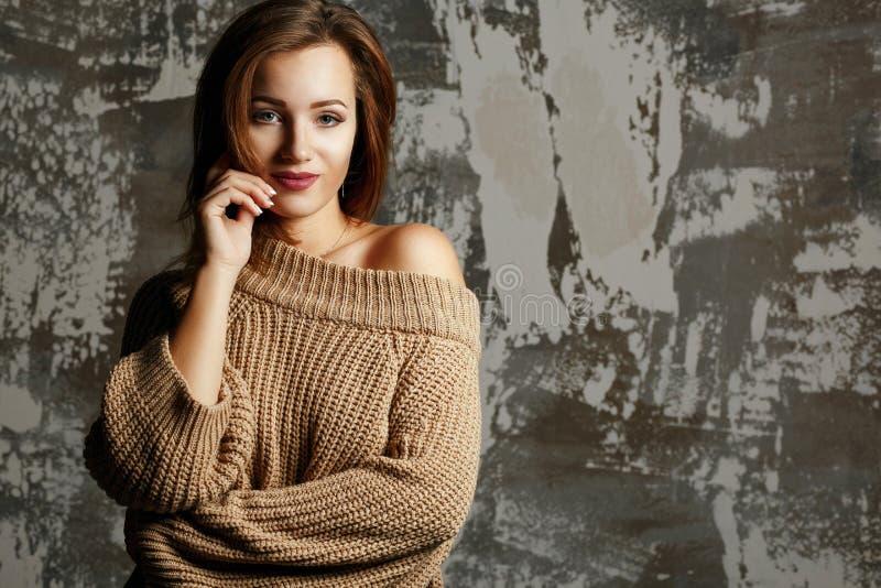Vrij jonge vrouw die gebreide sweater met naakte schouder dragen, die met schaduwen stellen Lege ruimte stock foto
