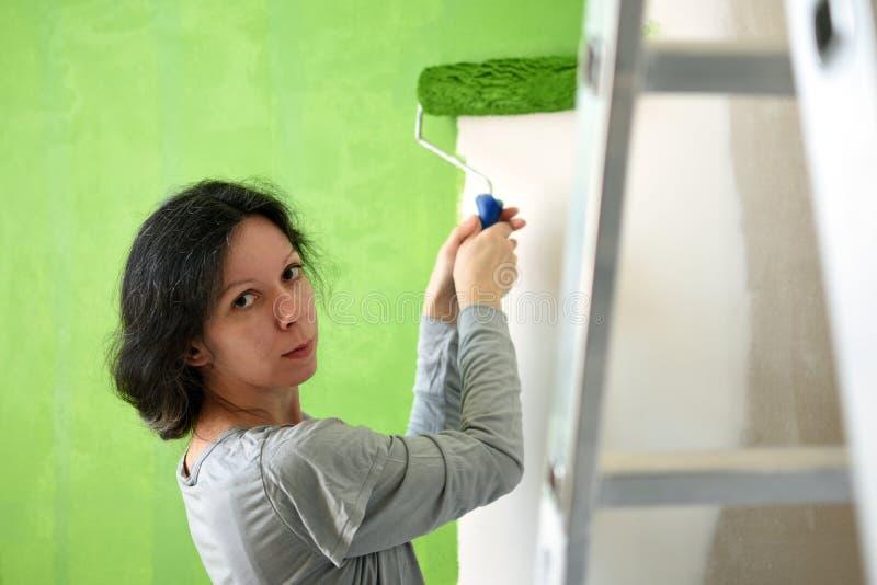 Vrij jonge vrouw die groene binnenlandse muur met rol in een nieuw huis schilderen royalty-vrije stock fotografie