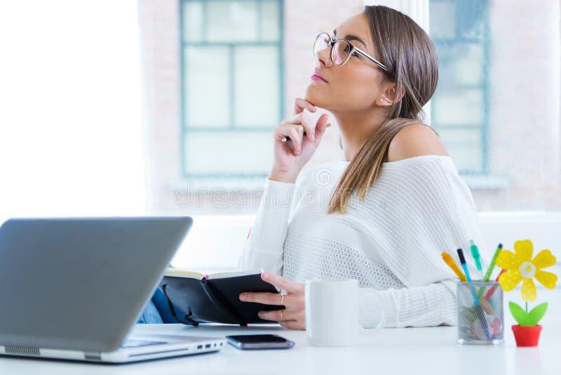 Vrij jonge vrouw die in haar bureau werkt stock fotografie
