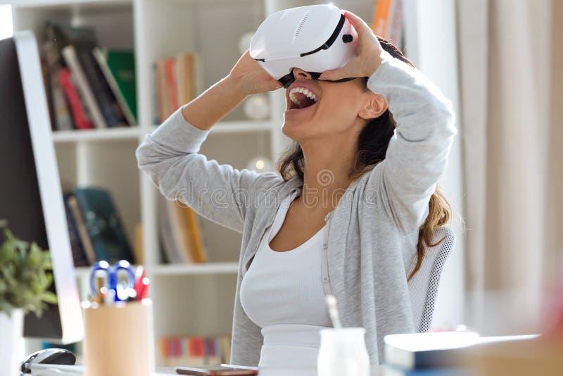 Vrij jonge vrouw die haar virtuele werkelijkheidshoofdtelefoon thuis met behulp van royalty-vrije stock afbeeldingen
