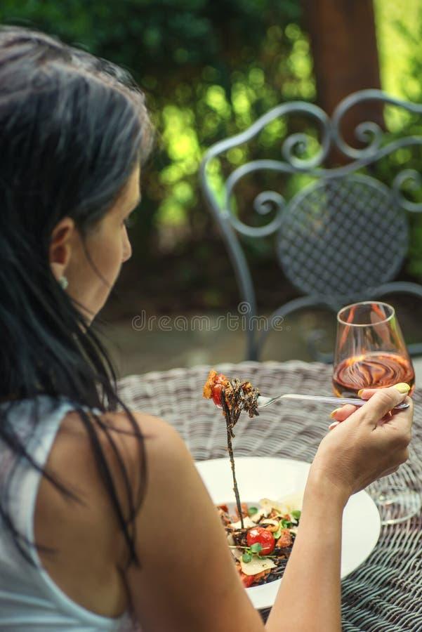 Vrij jonge vrouw die Italiaanse die deegwaren met tomatensaus en parmezaanse kaas eten, met glas wijn, productfotografie voor res royalty-vrije stock afbeeldingen