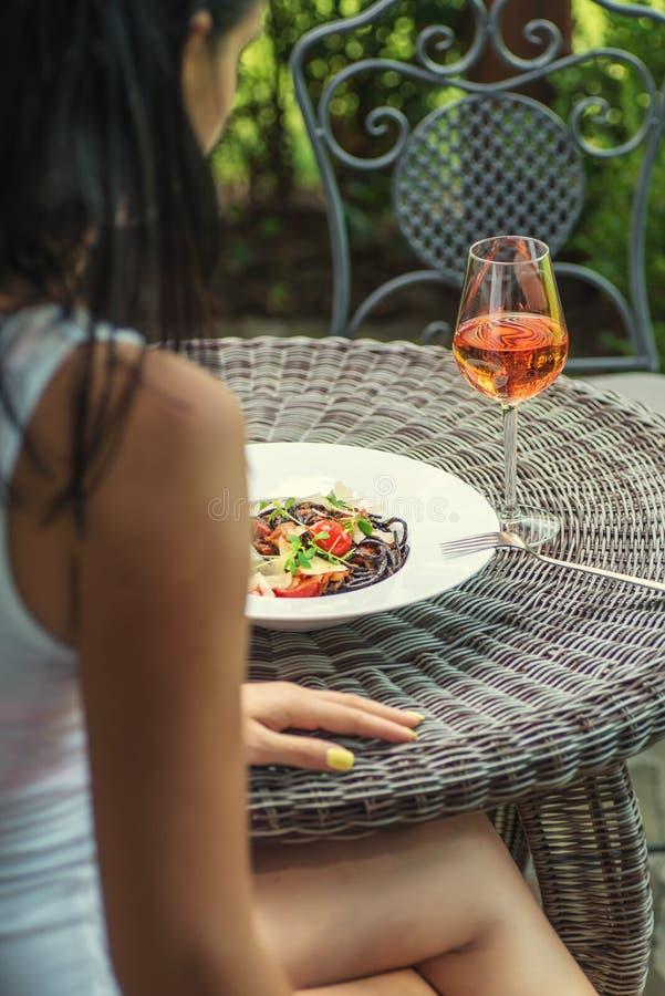 Vrij jonge vrouw die Italiaanse die deegwaren met tomatensaus en parmezaanse kaas eten, met glas wijn, productfotografie voor res stock afbeelding