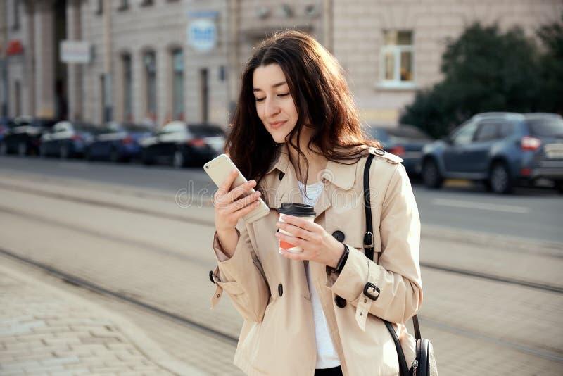 Vrij jonge vrouw die meeneemkoffiekop drinken die in openlucht, op de telefoon spreken, royalty-vrije stock foto