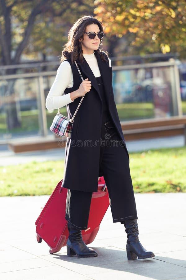 Vrij jonge vrouw die met koffer aan het station lopen royalty-vrije stock foto