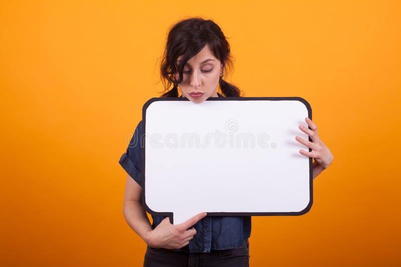 Vrij jonge vrouw die neer op gedachte bel in studio over gele backgound kijken royalty-vrije stock foto
