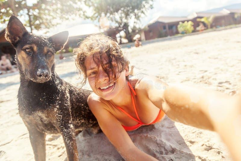 Vrij jonge vrouw die selfie met haar hond op het strand bij zon doen royalty-vrije stock foto's
