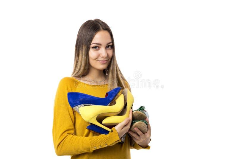 Vrij jonge vrouw die vele schoenen over witte achtergrond houden stock afbeelding