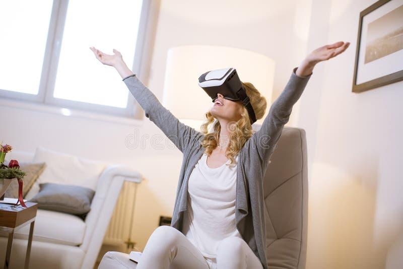 Vrij jonge vrouw die virtuele werkelijkheidsbeschermende brillen dragen stock afbeelding