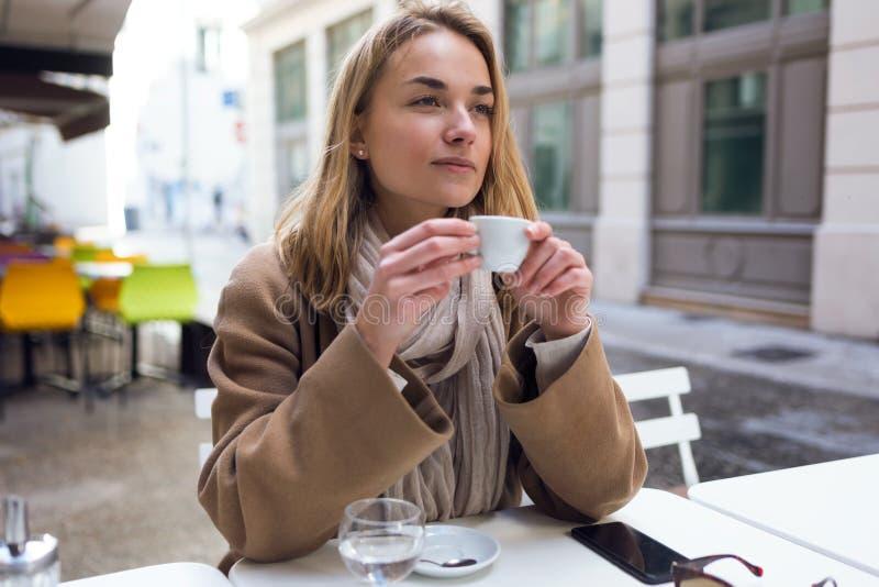 Vrij jonge vrouw die zijdelings terwijl drinkende kop van koffie op het terras van een koffiewinkel kijken stock afbeelding