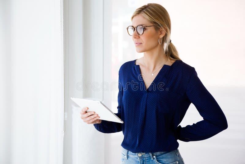 Vrij jonge vrouw die zijdelings terwijl thuis het gebruiken van haar digitale tablet kijken royalty-vrije stock afbeeldingen