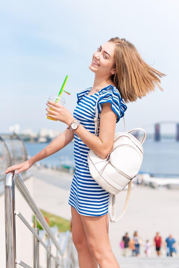 Vrij jonge vrouw het drinken fruitcocktail en het genieten van van zon en goede warme dag dichtbij de rivier, de zomervakantie, v royalty-vrije stock foto's