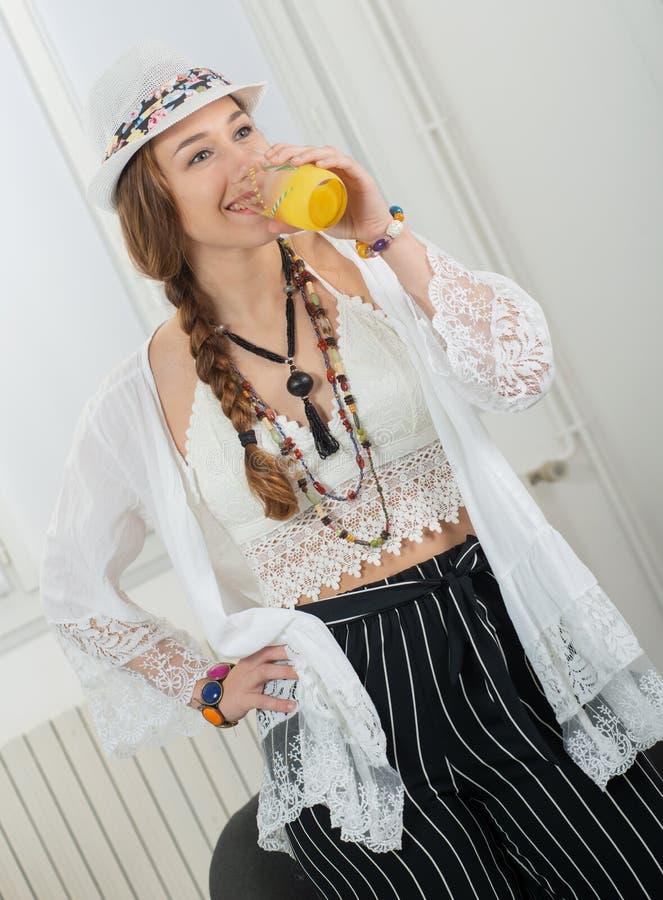 Vrij jonge vrouw met een de drankenglas van de de zomerhoed jus d'orange stock foto