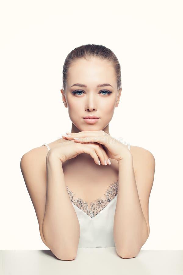 Vrij jonge vrouw met gezonde huid, natuurlijke make-up en Franse manicurespijkers bij handen het ontspannen stock afbeeldingen