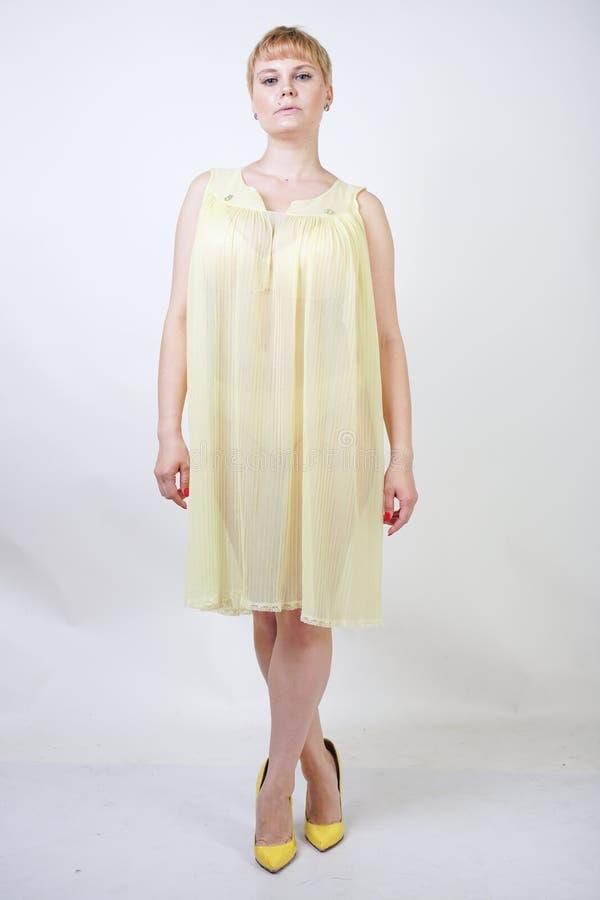 Vrij jonge vrouw met kort haar en mollig lichaam dat transparante nachtjapon draagt en op witte studio alleen achtergrond stelt b royalty-vrije stock afbeeldingen