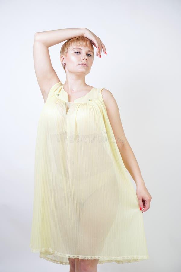 Vrij jonge vrouw met kort haar en mollig lichaam die transparante nachtjapon dragen en op witte studio alleen achtergrond stellen royalty-vrije stock afbeeldingen