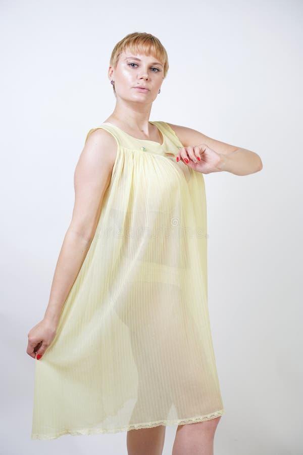 Vrij jonge vrouw met kort haar en mollig lichaam die transparante nachtjapon dragen en op witte studio alleen achtergrond stellen stock foto