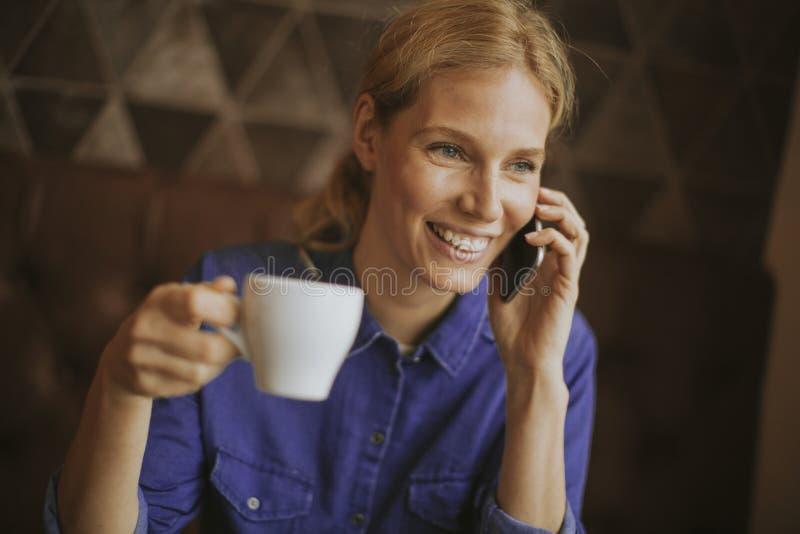 Vrij jonge vrouw met mobiele telefoon in de koffie stock foto