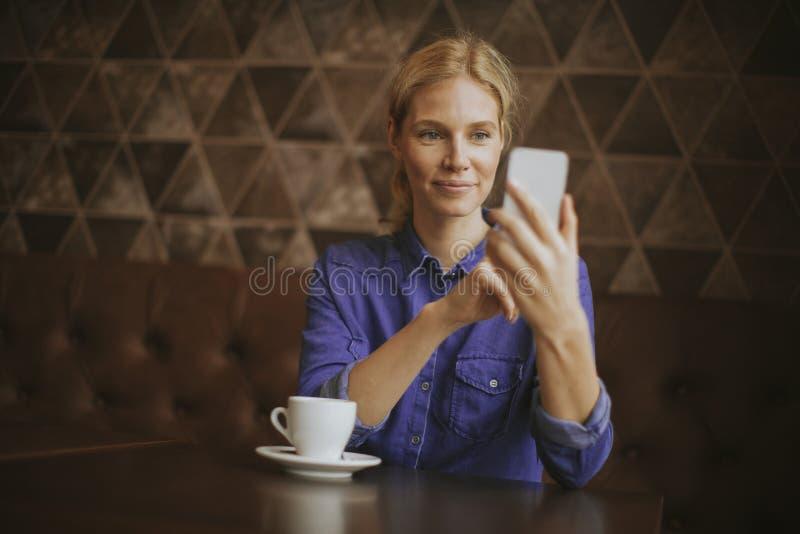 Vrij jonge vrouw met mobiele telefoon in de koffie stock afbeeldingen