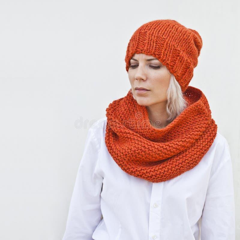 Vrij jonge vrouw in warme sinaasappel gebreide hoed en haarband royalty-vrije stock fotografie