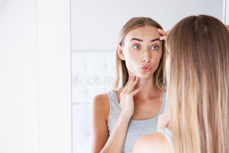 Vrij jonge vrouw wat betreft haar gezicht terwijl het bekijken de spiegel, schoonheidsconcept, huidzorg, plastische chirurgie royalty-vrije stock fotografie