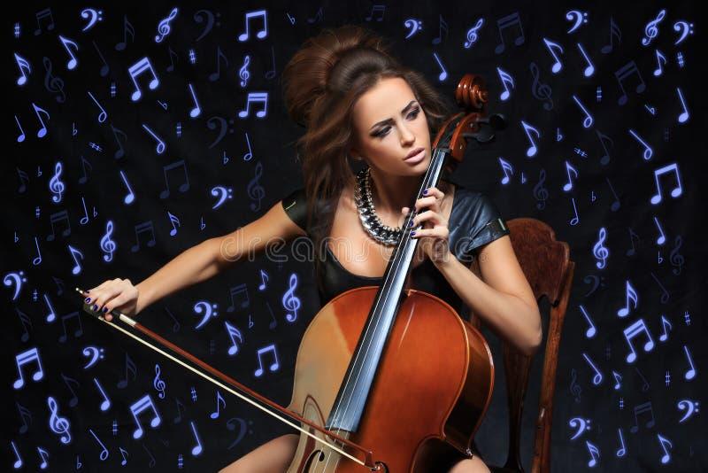 Vrij jonge vrouwelijke musicus die de cello spelen royalty-vrije stock foto