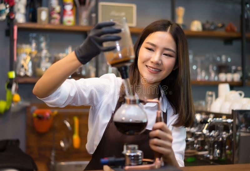 Vrij jonge vrouwen Kaukasische barista bereidt koffiesifon voor beweegt stock fotografie