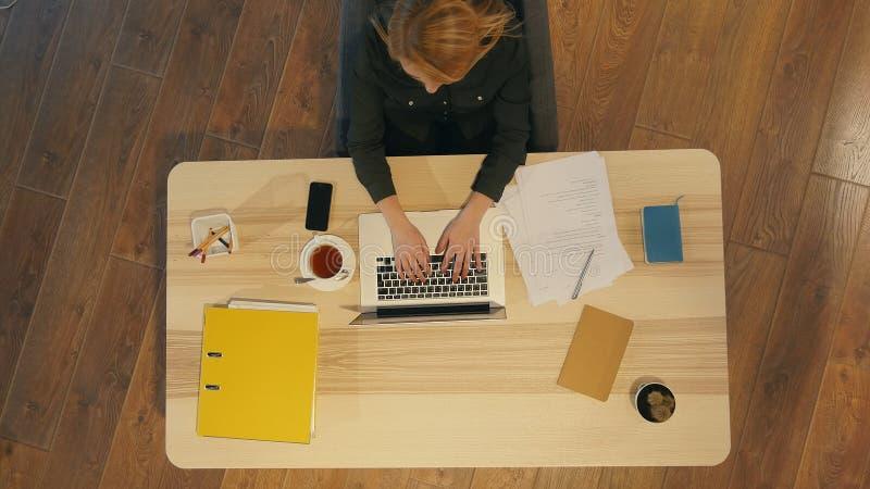 Vrij jonge vrouwenzitting bij bureau en het typen op laptop stock foto's