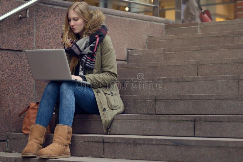 Vrij jonge vrouwenzitting op stappen in stad stock foto