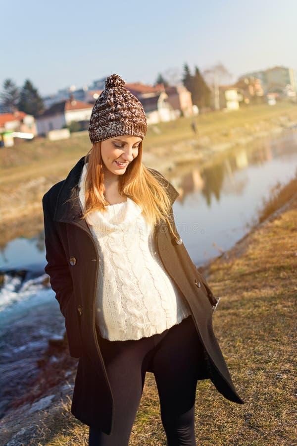 Vrij jonge zwangere vrouw die zich door de rivier bevinden stock afbeeldingen